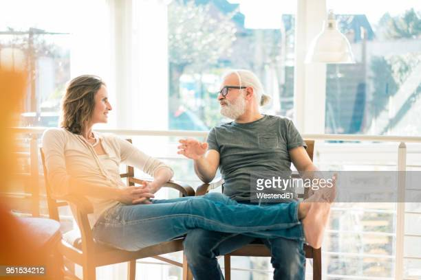 relaxed mature couple talking on chairs at home - 50 59 jaar stockfoto's en -beelden