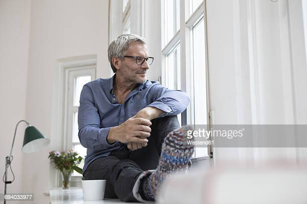 Relaxed mature man at home looking out of window
