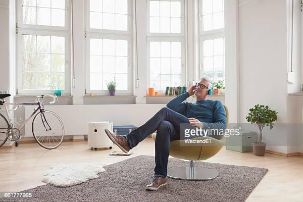 relaxed mature man at home sitting in chair listening to music - 50 54 jahre stock-fotos und bilder