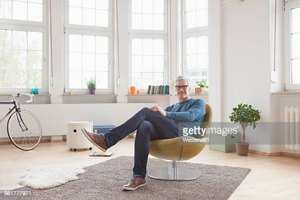 Relaxed mature man at home sitting in chair