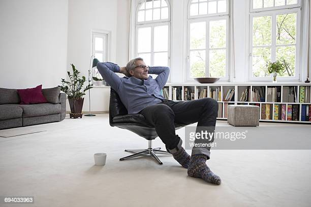 relaxed mature man at home sitting in chair - wohlstand stock-fotos und bilder