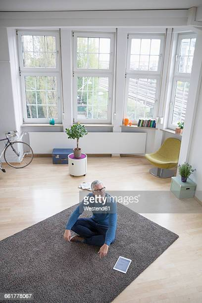 Relaxed mature man at home sitting on floor