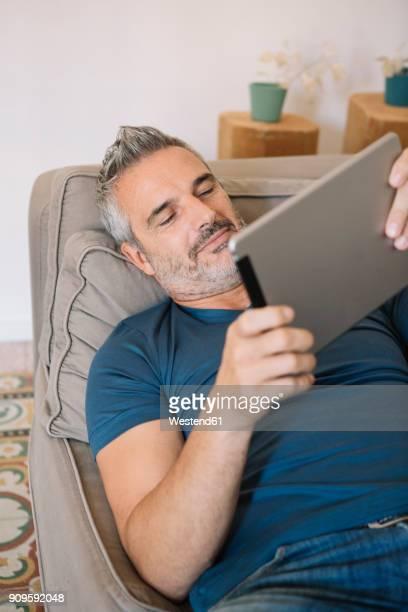 relaxed mature man at home using tablet - solo un uomo maturo foto e immagini stock