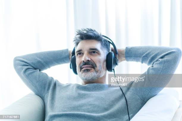 Relaxed mature man at home wearing headphones