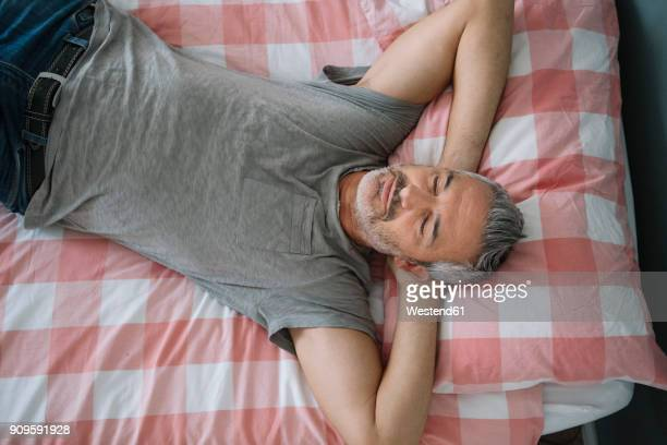 Relaxed mature man sleeping on bed