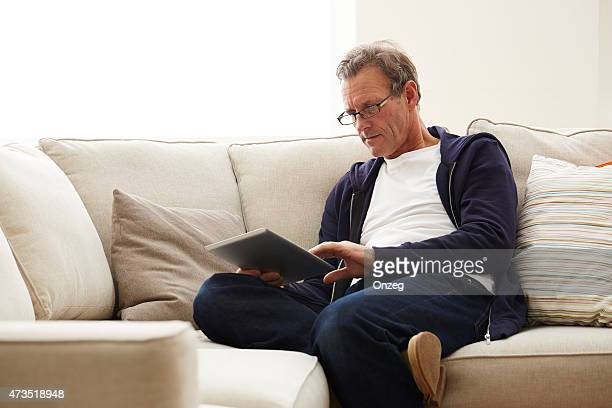 relaxed mature man using digital tablet at home - one mature man only stock photos and pictures