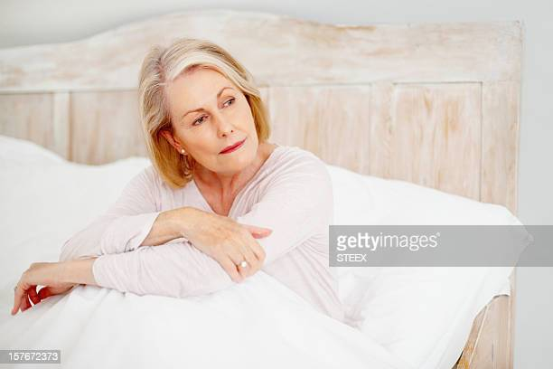 Relaxed mature woman in bed looking away
