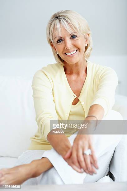 Relaxed mature woman sitting in couch against grey