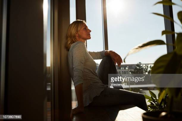 relaxed mature woman sitting in sunlight at home - einfaches leben stock-fotos und bilder