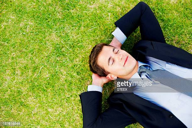 Relaxed mid adult business man sleeping peacefully on grass