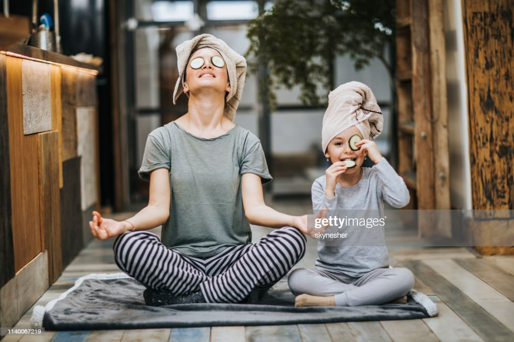 Relaxed mother and daughter exercising Yoga in the morning at home. : Foto de stock