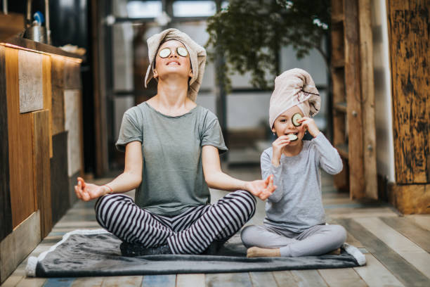 relaxed mother and daughter exercising yoga in the morning at home. - mom and daughter stock pictures, royalty-free photos & images