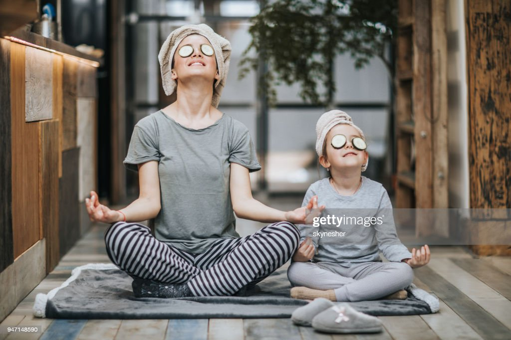 Relaxed mother and daughter exercising Yoga in the morning at home. : Stock Photo