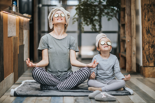 Relaxed mother and daughter exercising Yoga in the morning at home. 947148590