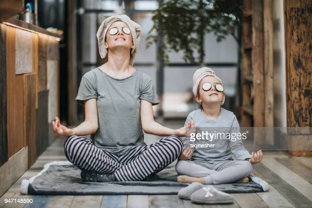 relaxed mother and daughter exercising yoga in the morning at home. - zen like stock pictures, royalty-free photos & images
