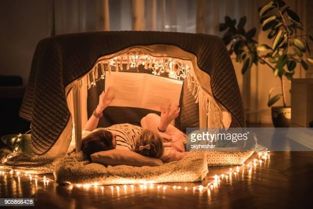 mãe relaxada e filha lendo um livro em uma barraca na sala. - narração de histórias - fotografias e filmes do acervo