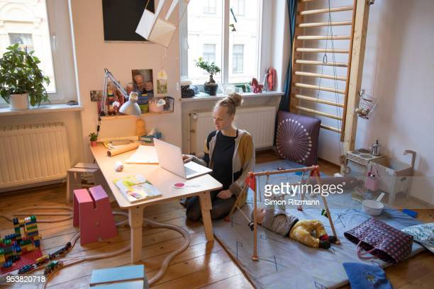 relaxed mother using laptop at home while baby is playing next to her - multi tasking stock pictures, royalty-free photos & images