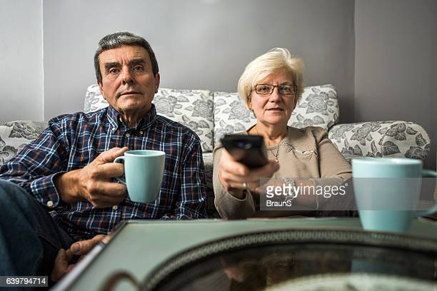 Relaxed old couple watching TV at their home.
