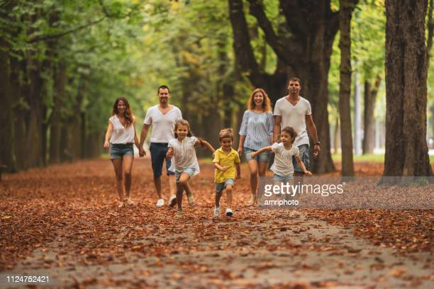 relaxed partenting, parents with children in public park - avenue stock pictures, royalty-free photos & images