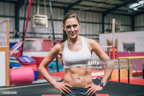 relaxed portrait of smiling mid adult female athlete in gym - floor gymnastics stock pictures, royalty-free photos & images