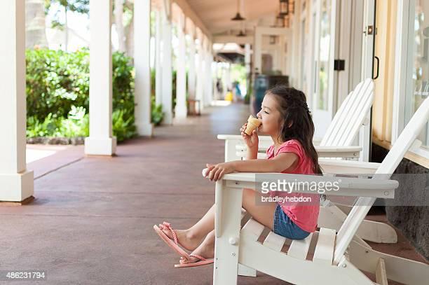 Entspannte hübsche kleine Mädchen isst ein Eis-cream cone