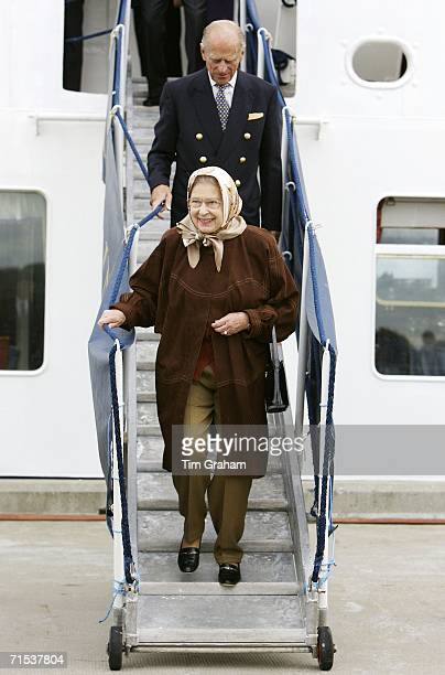 Relaxed Queen Elizabeth II in suede coat headscarf and trousers with Prince Philip Duke of Edinburgh leaves the Hebridean Princess at Stornoway after...