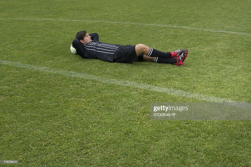 Relaxed referee lying on soccer field : Photo