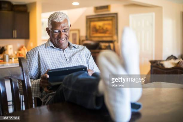 relaxed senior black man working on tablet in kitchen at home - old man feet stock pictures, royalty-free photos & images