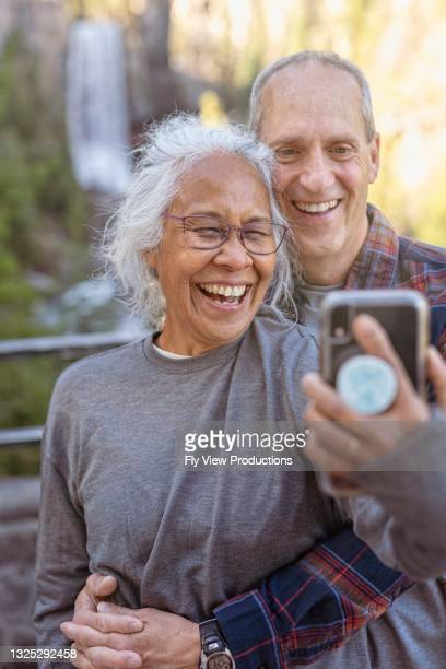 relaxed senior couple on vacation taking a selfie by waterfall - hawaiian waterfalls stock pictures, royalty-free photos & images