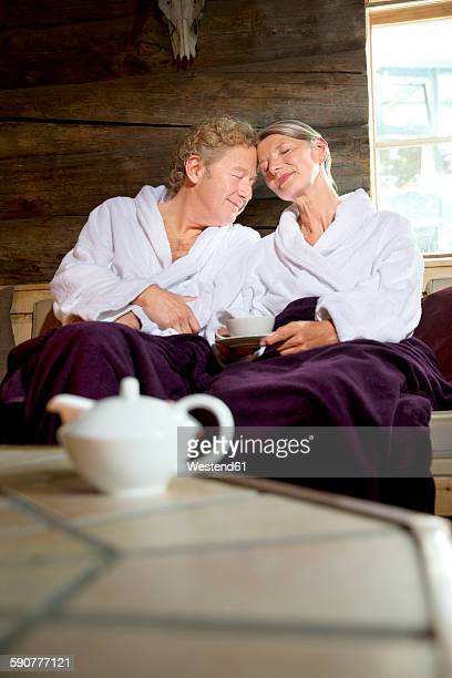 Relaxed senior couple sitting on bench in bathrobes