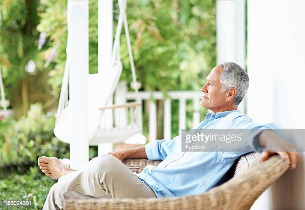 Relaxed senior man sitting on a wicker chair at porch