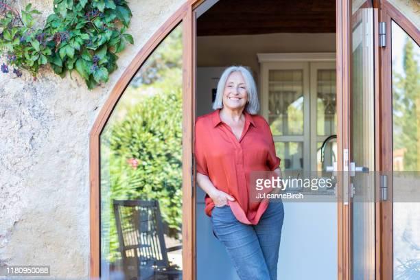 ontspannen senior spaanse vrouw staande in binnenplaats deuropening - handen in de zakken stockfoto's en -beelden