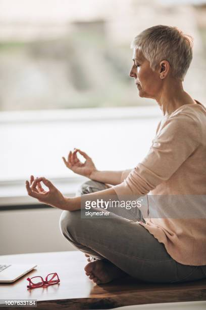 ontspannen senior vrouw yoga uitoefenen op de tabel thuis. - lotuspositie stockfoto's en -beelden