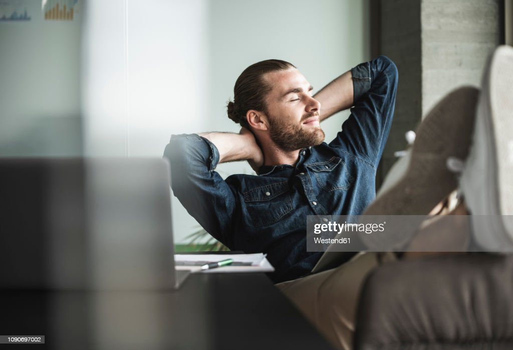Relaxed smiling businessman sitting in office with closed eyes : Foto de stock
