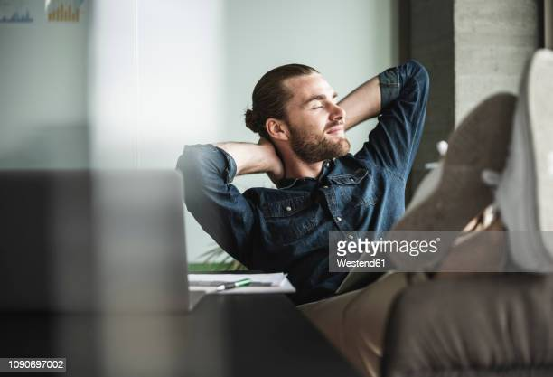 relaxed smiling businessman sitting in office with closed eyes - pauze nemen stockfoto's en -beelden