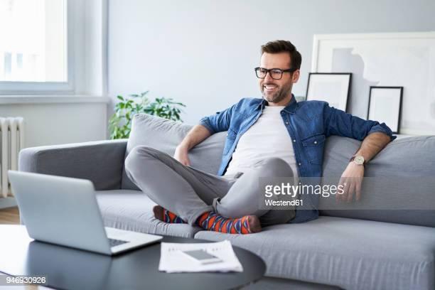 relaxed smiling man sitting on sofa looking at laptop - bonne nouvelle photos et images de collection