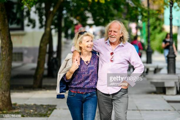 relaxed smiling seniors walking together in ljubljana - v neck stock pictures, royalty-free photos & images