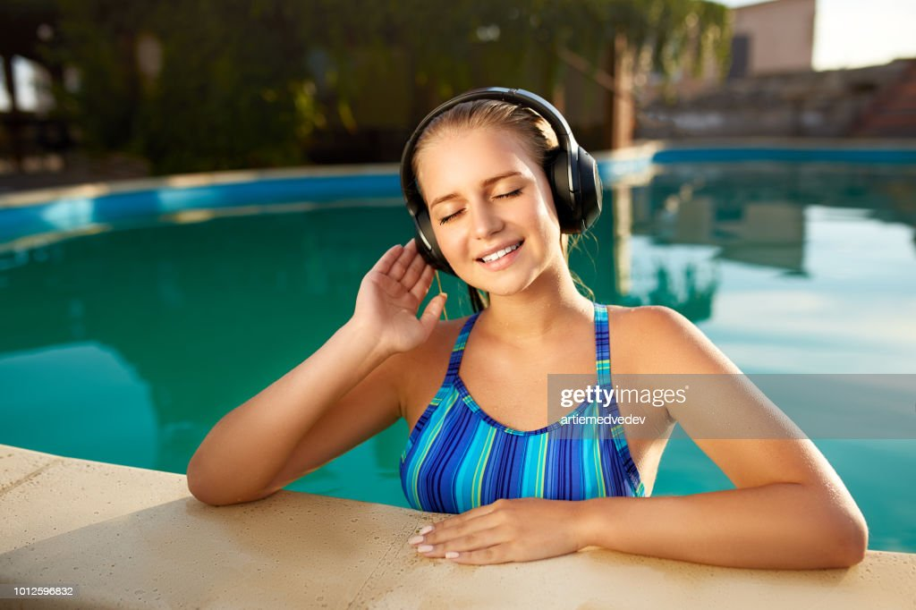 Relaxed smiling woman listening to music in headphones bathing in swimming pool. Blonde girl enjoys favourite song with goosebumps on skin. Waterproof headphones with touch control mobility concept : Stock Photo