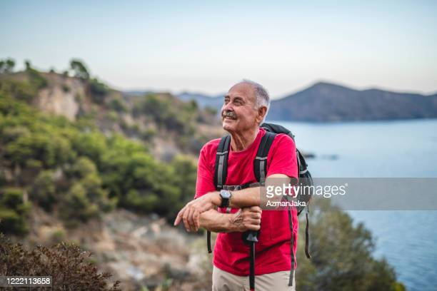 relaxed spanish senior male backpacker on coastal trail - mediterranean sea stock pictures, royalty-free photos & images