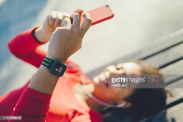 relaxed sportswoman enjoying good music - smart watch stock pictures, royalty-free photos & images