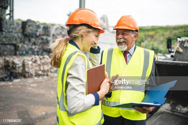 relaxed waste management experts sharing findings onsite - waste management stock pictures, royalty-free photos & images