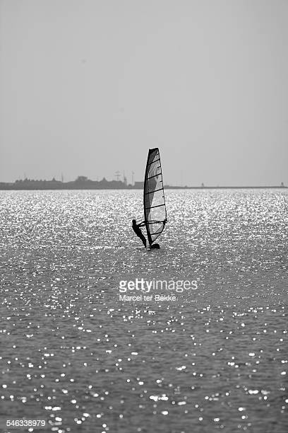 Relaxed windsurfer slowly surfing home on a calm lake