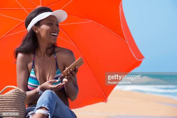 Entspannte Frau Sonnenschutz Creme auftragen, am sonnigen Strand.