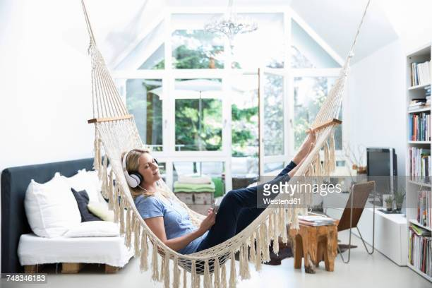relaxed woman at home lying in hammock listening to music - comfortabel stockfoto's en -beelden