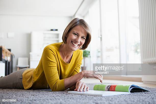 Relaxed woman at home lying on floor reading magazine