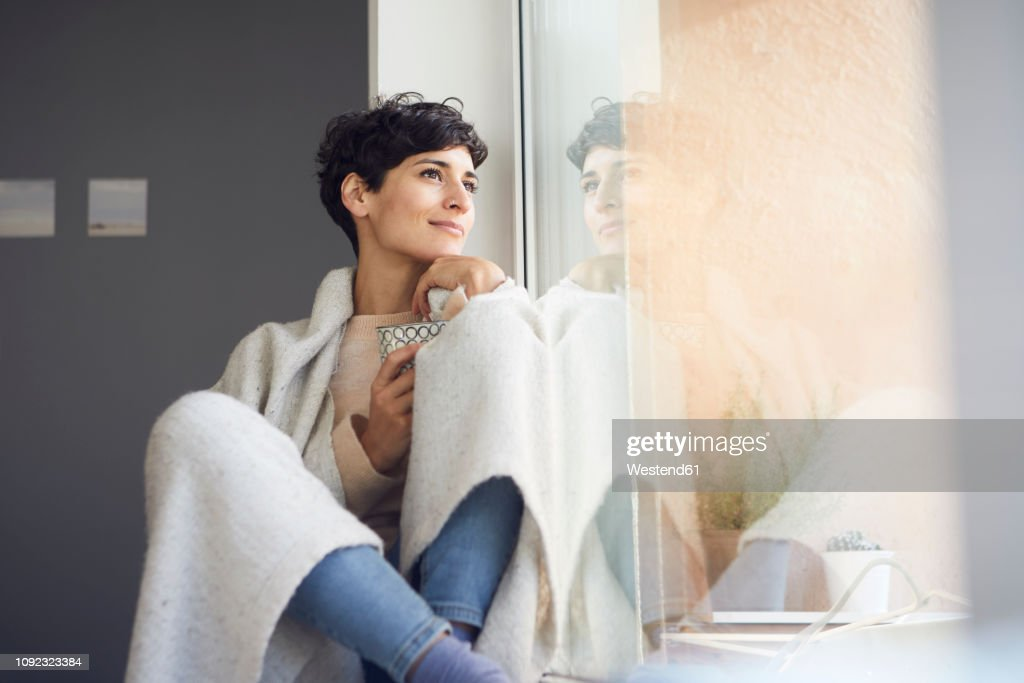 Relaxed woman at home sitting at the window : Stock-Foto