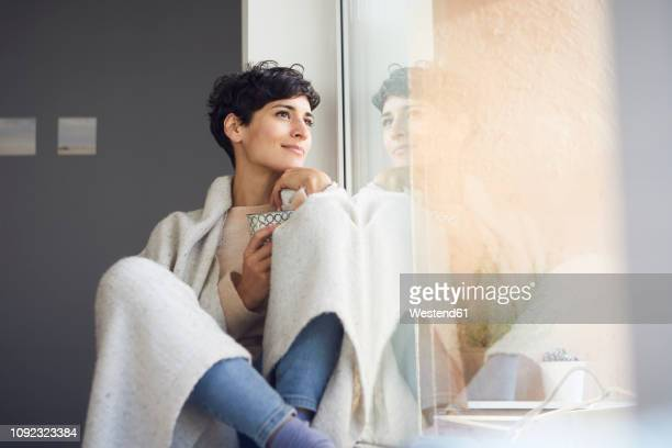 relaxed woman at home sitting at the window - wochenendaktivität stock-fotos und bilder