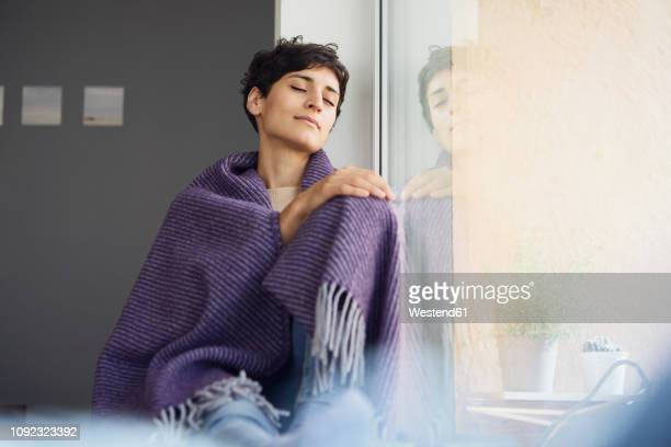 relaxed woman at home sitting at the window - convalescenza foto e immagini stock