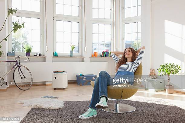 relaxed woman at home sitting in chair - cadeira - fotografias e filmes do acervo