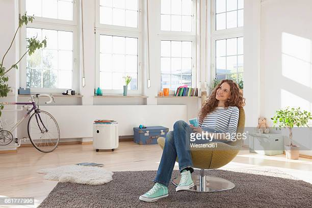 Relaxed woman at home sitting in chair